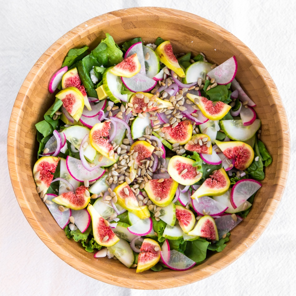 Summer fig salad with figs, radishes, cucumber, red onion, spinach, romaine, sunflower seeds, avocado, and feta cheese